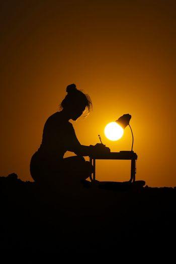 Silhouette man sitting against orange sky during sunset