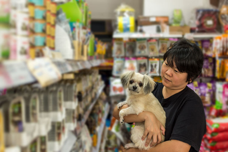 Woman with dog standing in supermarket