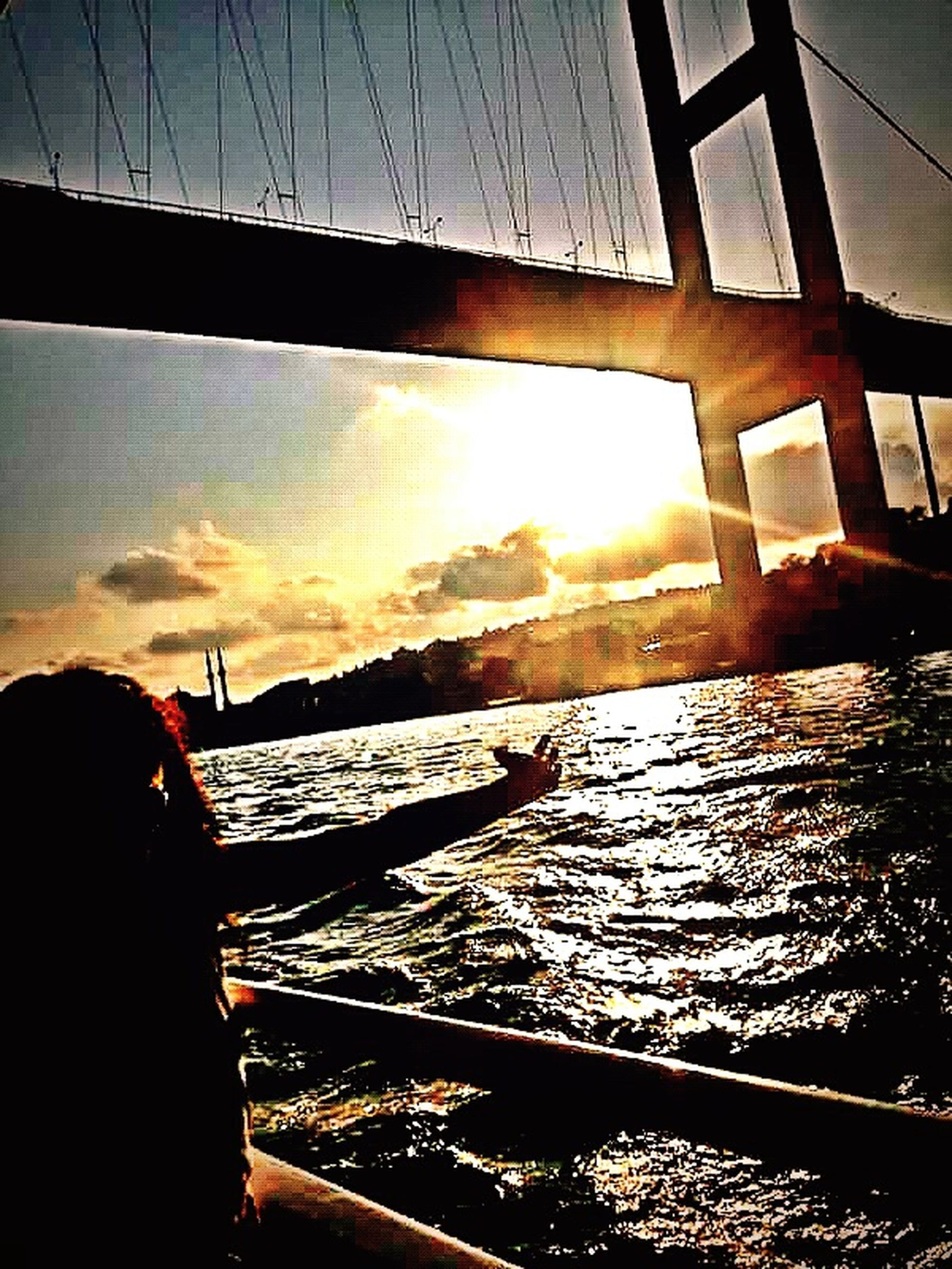 water, transportation, sunset, sky, mode of transport, silhouette, reflection, nautical vessel, sea, built structure, river, sun, travel, sunlight, boat, connection, architecture, vehicle interior