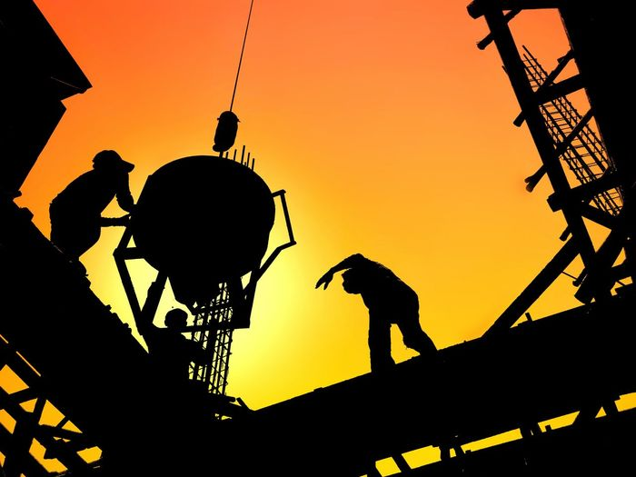 Silhouette construction workers are casting concrete on top of building structure with blurred sundown sky background on construction and occupation concept House Infrastructure Construction Workers Casting Concrete Top Of Building Structure Reinforcement High Low Angle View Technology Crane Bucket Blur Background Morning Sundown Evening Occupation Mason Profession Team Group Sunset Silhouette Occupation Sky High Section Sunrise - Dawn