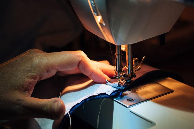 Cropped hands using sewing machine in darkroom