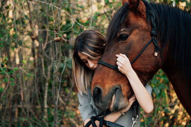 Young woman embracing horse while standing outdoors