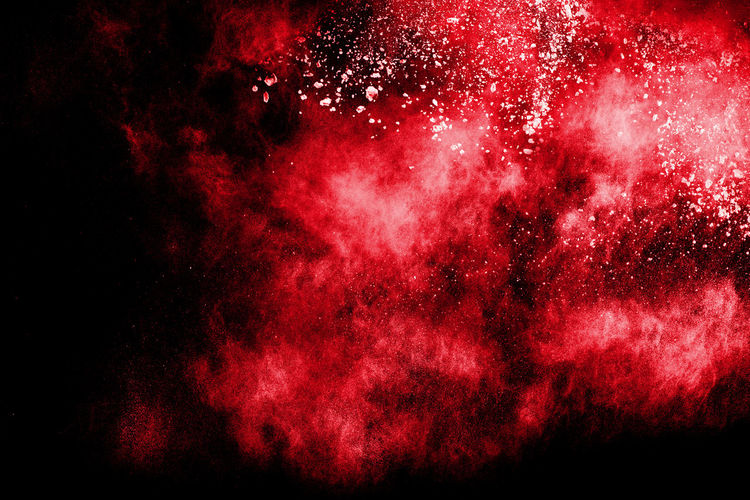 Close-up of exploding dust against black background