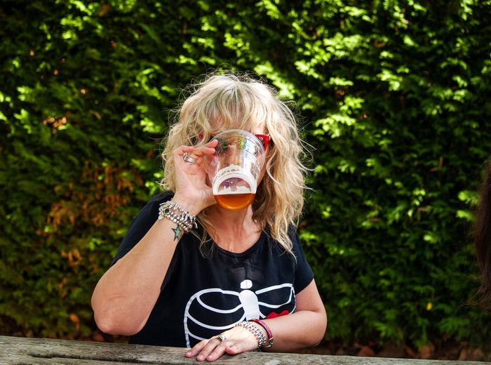 Woman drinking beer in glass against plants