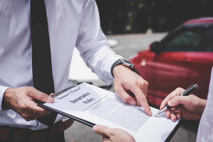 Midsection of customer signing contract while insurance agent holding clipboard