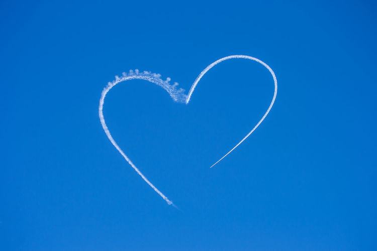 Low angle view of heart shape vapor trail against clear blue sky