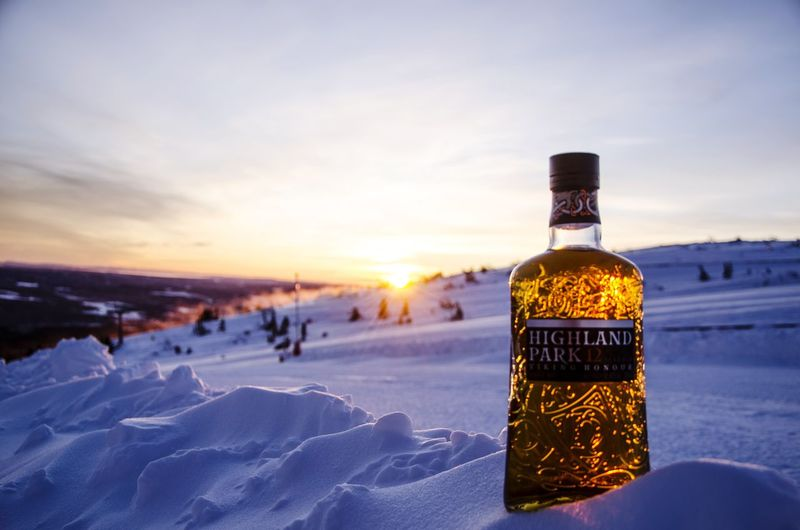 Close-up of bottle against snow during sunset