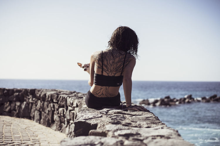 Rear view of woman on beach against clear sky
