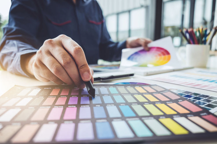 Graphic Adult Business Close-up Color Chart Colorful Creativity Design Professional Designer  Desk Drawing Focus On Foreground Hand Holding Human Body Part Human Hand Indoors  Men Occupation One Person Pantone Paper Pointing Selective Focus Swatch
