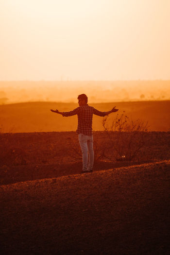 One Person Sky Land Field Leisure Activity Real People Standing Human Arm Lifestyles Sunset Rear View Full Length Arms Outstretched Nature Landscape Limb Beauty In Nature Casual Clothing Environment Freedom Outdoors