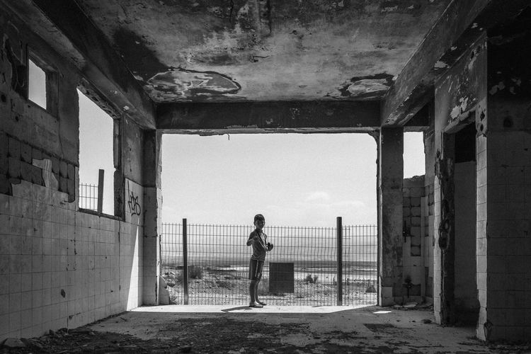 Full length of boy standing at abandoned building