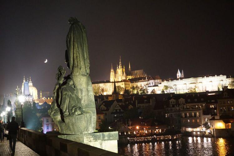 Statue of illuminated city against sky at night