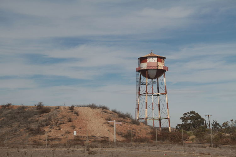 Water tower on land against sky