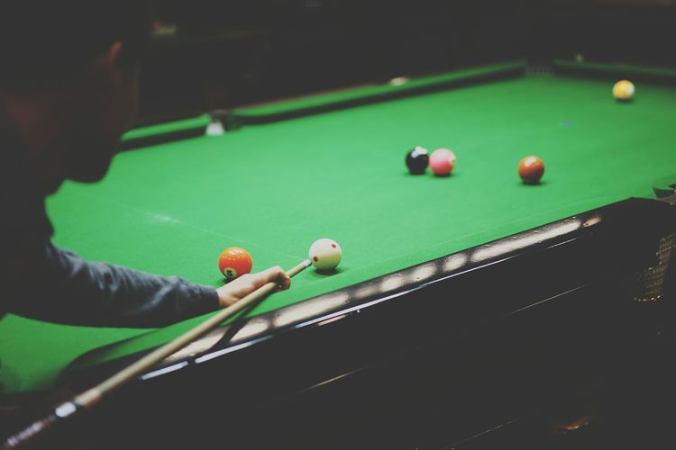 Cropped Man Aiming Ball At Pool Table