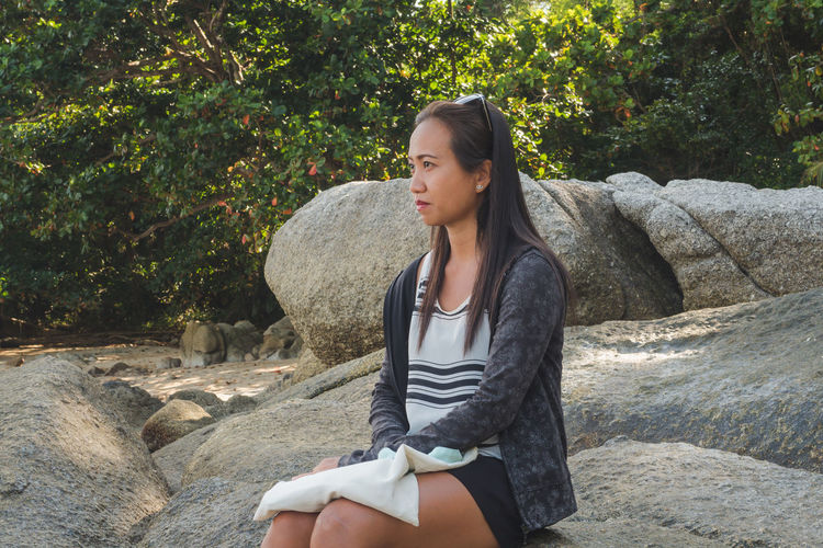 Young woman looking away while sitting on rock