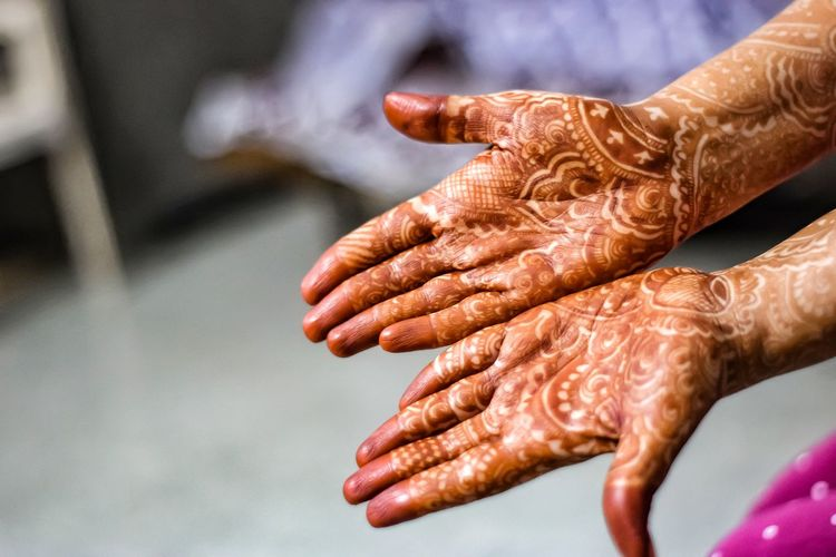 Cropped image of woman showing henna tattoo on hands