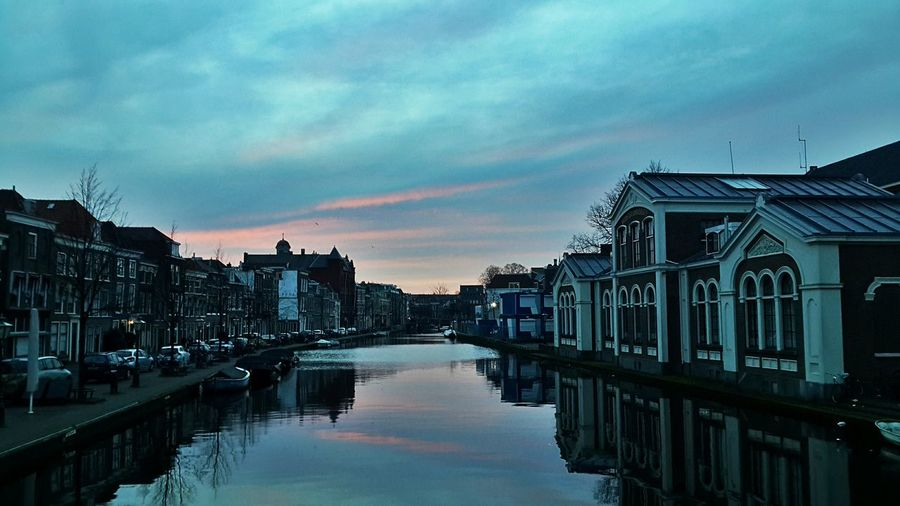 Canal Amidst Houses Against Cloudy Sky During Sunset