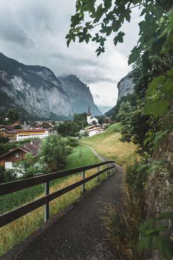 Scenic view over Lauterbrunnen Valley, Switzerland Lauterbrunnen Valley Plant Mountain Sky Tree Nature Architecture Beauty In Nature Built Structure Scenics - Nature Cloud - Sky Environment Mountain Range Landscape Day Growth Land No People Grass Tranquility Railing Outdoors Church Scenics Switzerland