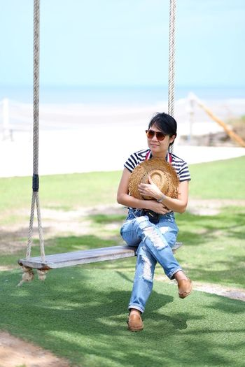 Woman looking away with hat while sitting on swing at beach