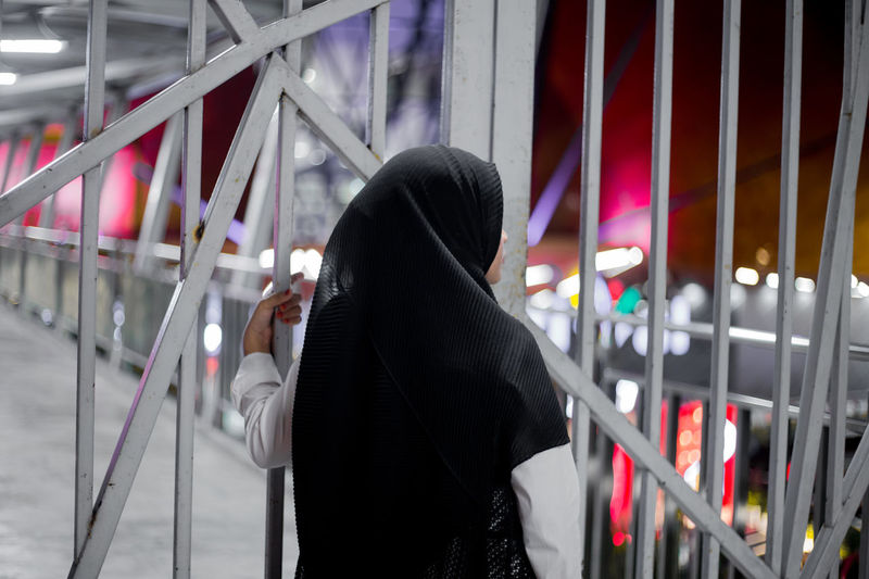 Rear view of woman in hijab standing by gate