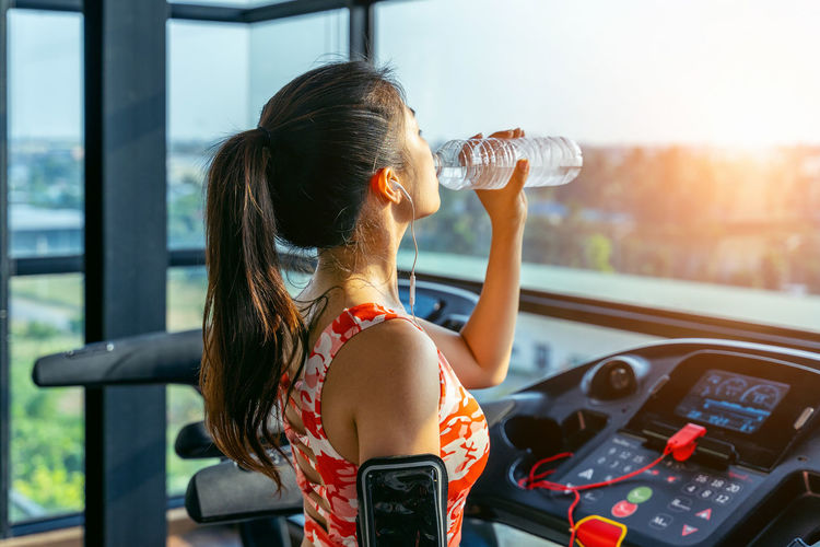Young woman drinking water in the gym. Exercise concept. Transportation One Person Mode Of Transportation Real People Women Adult Car Lifestyles Headshot Land Vehicle Day Motor Vehicle Glass - Material Portrait Holding Young Women Rear View Focus On Foreground Hairstyle Hair Outdoors