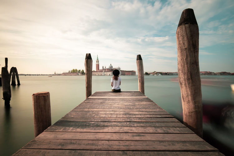 Rear view of woman sitting by grand canal on pier