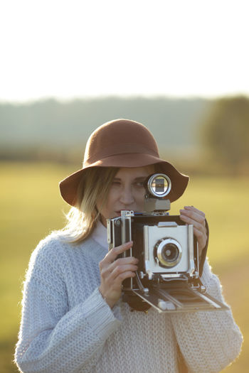 Adult Blond Hair Camera - Photographic Equipment Close-up Day Holding Leisure Activity Lifestyles Movie Camera Nature Old-fashioned One Person Outdoors People Photographer Photographing Photography Themes Portrait Real People Retro Styled Technology Young Adult Young Women