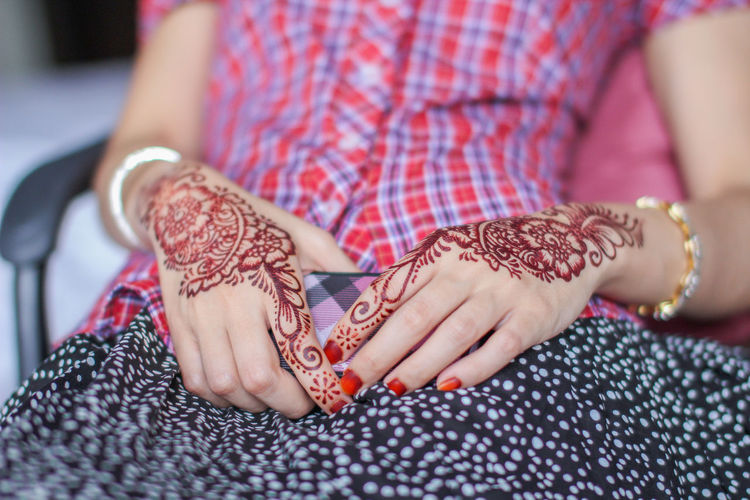 Midsection of woman with henna tattoo holding mobile phone