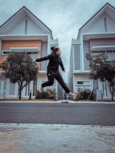 Man jumping by building against sky
