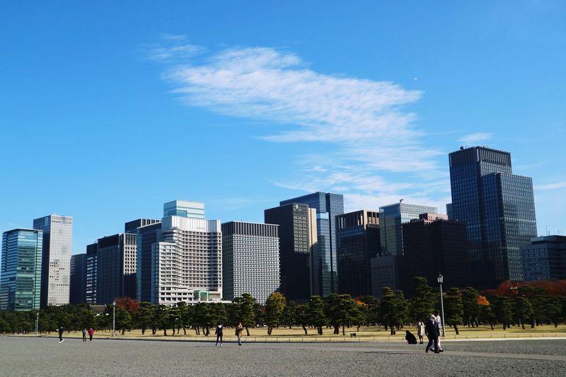 People walking in modern city against sky