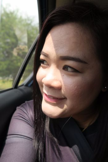 Close-up of smiling woman looking away while traveling in car