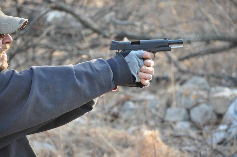 Close-up of man aiming pistol