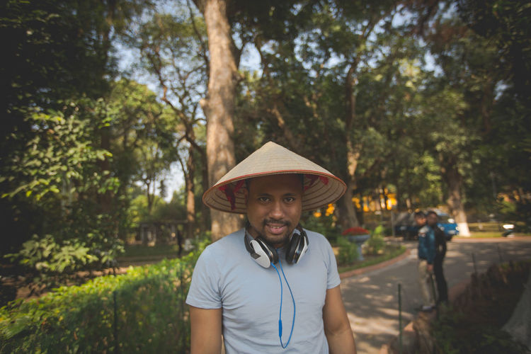 Portrait of man wearing asian style conical hat and headphones at park