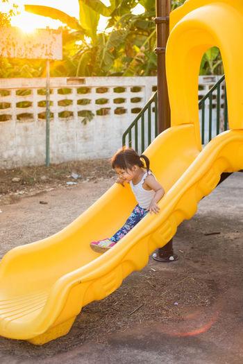Full Length Of Smiling Girl Standing At Slide