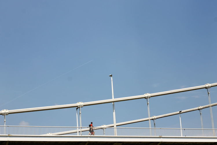 Man Walking On Bridge Against Blue Sky