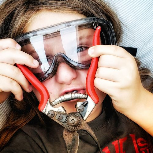 Close-up portrait of boy wearing protective eyewear while holding pruning shears