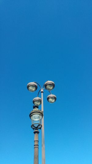 Low Angle View Of Lamp Posts Against Clear Blue Sky