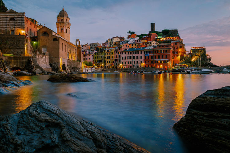Illuminated buildings by river against sky