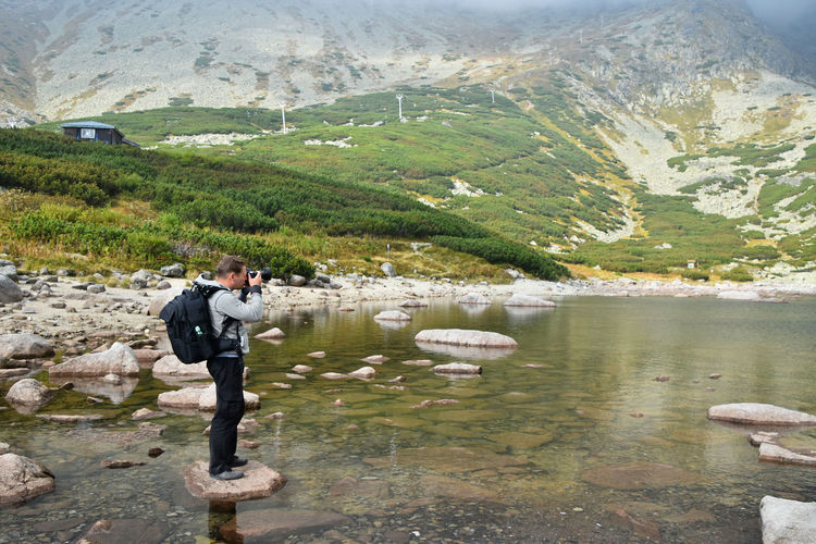 Side view of man photographing on rock in skalnate pleso lake