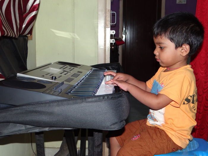 Side view of boy playing piano while sitting at home