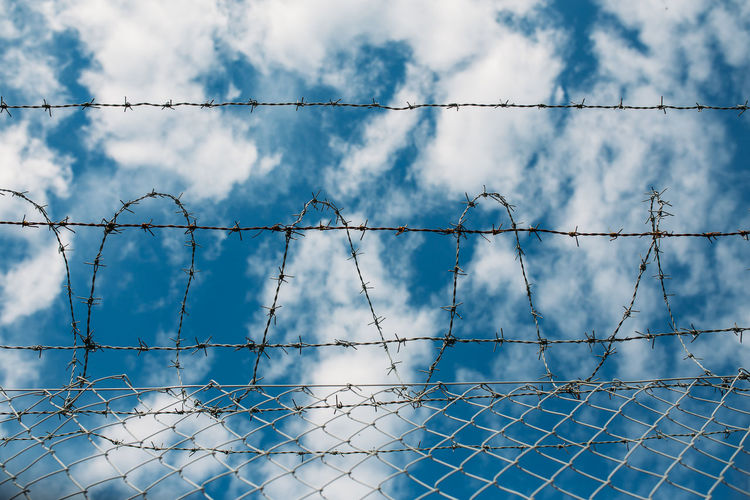 Low angle view of barbed wire fence against sky
