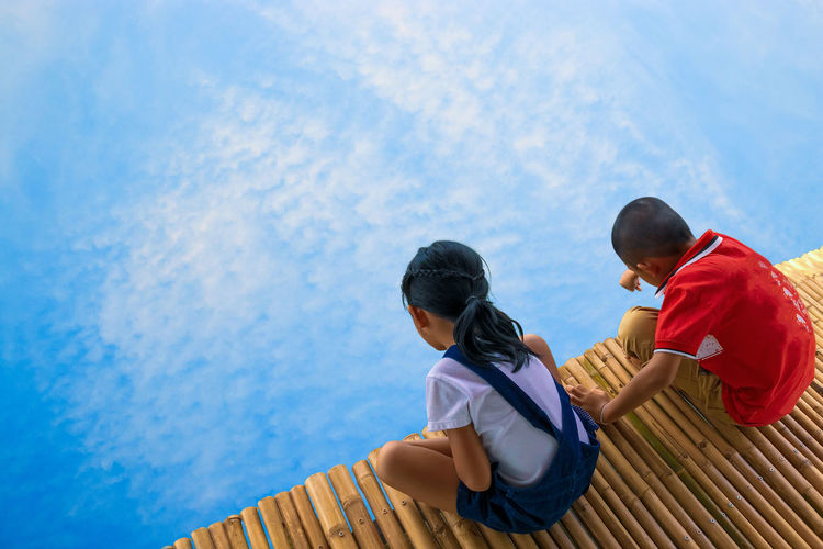 High angle view of siblings sitting on jetty over lake