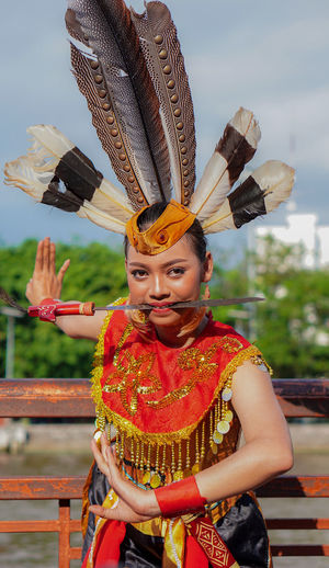 Portrait of smiling woman with costume standing outdoors