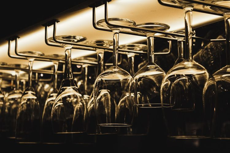 Indoors  Food And Drink Business Glass - Material No People Food And Drink Industry In A Row Transparent Container Glass Bottle Large Group Of Objects Close-up Upside Down Bar - Drink Establishment Illuminated Arrangement Metal Focus On Foreground Distillation