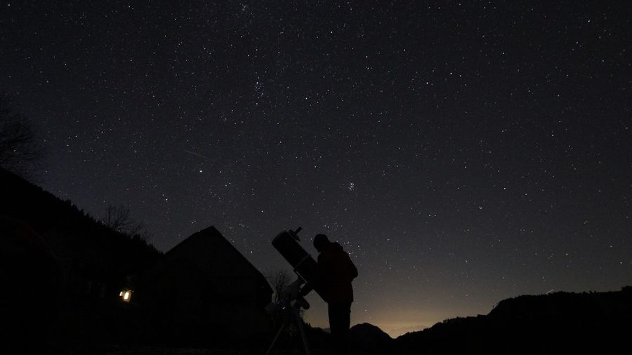 Silhouette man with telescope on field against star field