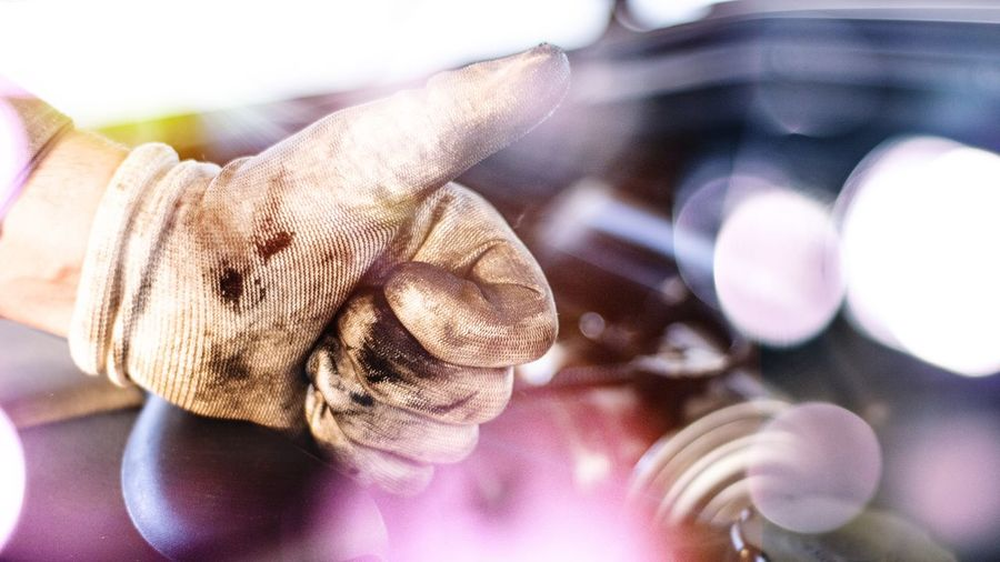 Cropped Hand Of Mechanic Gesturing Thumbs Up Sign By Car Engine