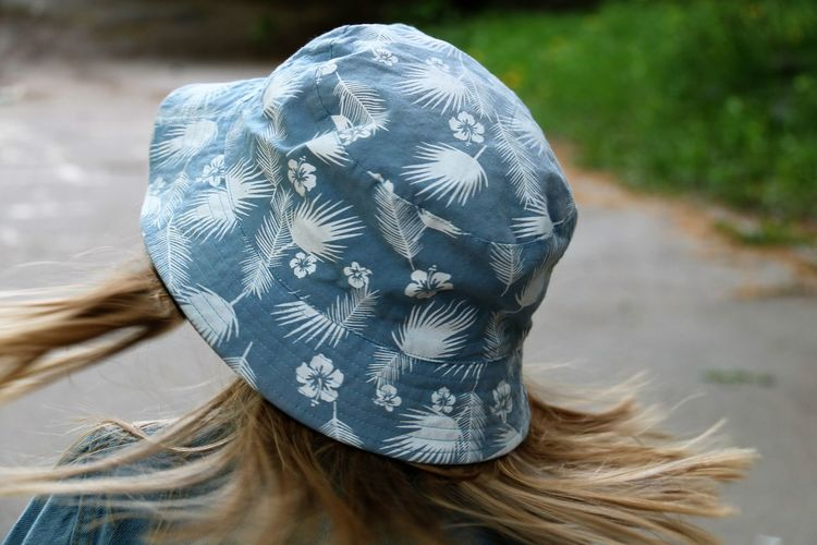 Close-up of woman wearing bucket hat while standing on footpath