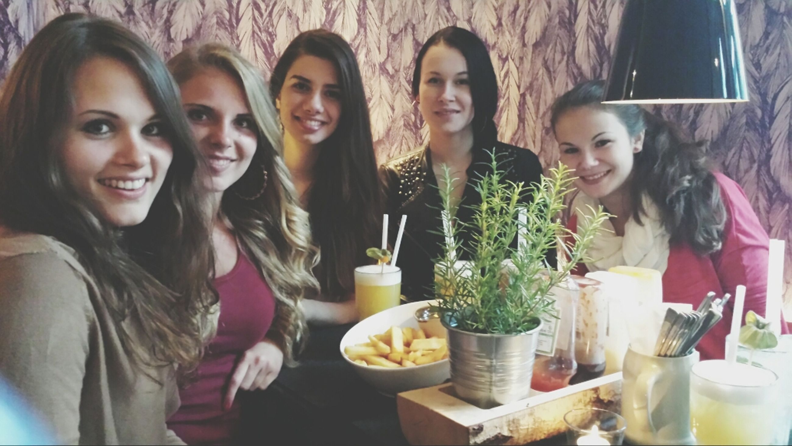 indoors, lifestyles, leisure activity, food and drink, togetherness, table, young adult, person, restaurant, young women, drink, friendship, casual clothing, bonding, sitting, portrait, smiling, front view