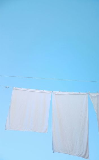 Close-Up Of Clothes Drying On Clothesline Against Clear Blue Sky