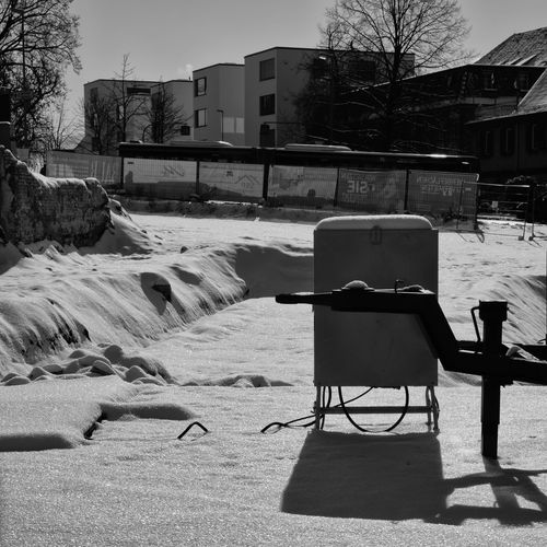 Empty chairs and tables against buildings